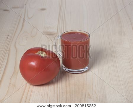 Red tomato and tomato juice on a wooden background