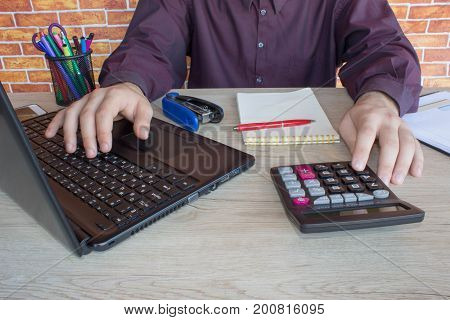 Business man doing finances on calculate analysis working with financial results Financial accounting sales forecast graph. Businessman Calculating Invoices Using Calculator