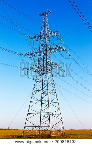 High Voltage Lines And Power Pylons In A Flat And Green Agricultural Landscape On A Sunny Day With C