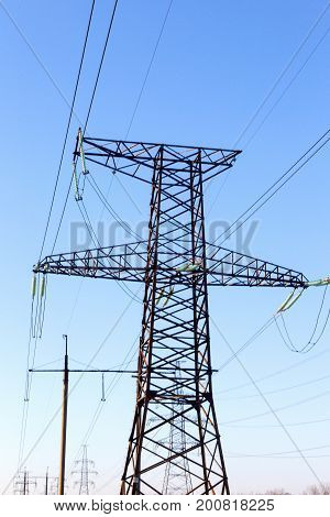 Power Lines. High Voltage Power Pylons Against Blue Sky And Sun Rays
