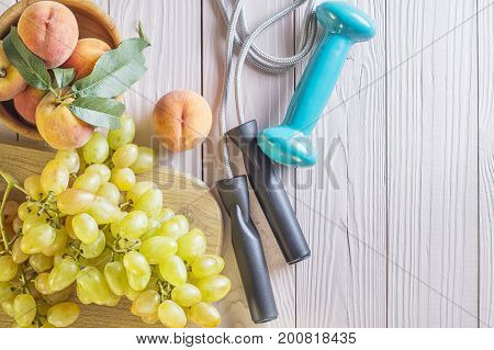 Healthy lifestyle concept with copy space top view. Healthy organic fruits peaches and grapes and sport fitness equipment dumbbells and jumping rope.