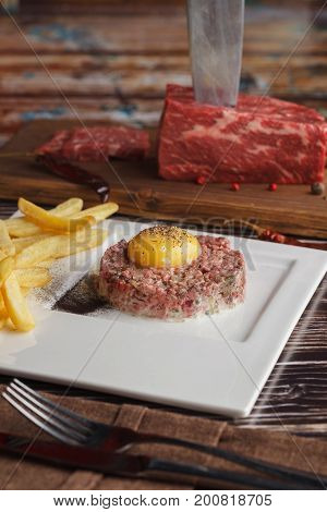 Tartar from marble beef with fried potato and yolk