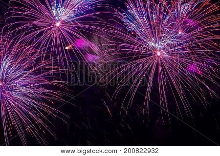 Close-up of vivid purple fireworks with sparks. Explosive pyrotechnic devices for aesthetic and entertainment purposes, art. Colored fireworks, holiday backdrop
