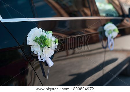 Boutonniere on the black wedding car handle