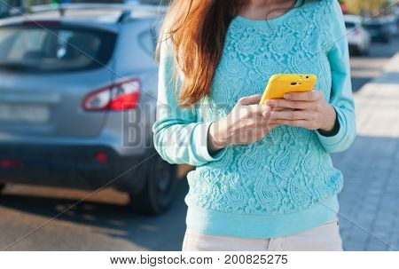 Woman with phone dialing message with cars.