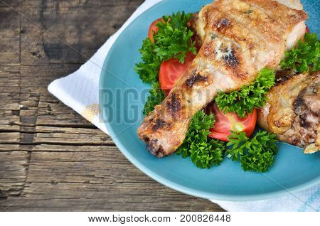 fried chicken plate with greens and tomatoes on wooden background
