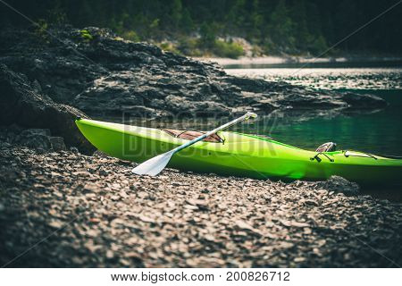 Green Pro Kayak on the Rocky Lake Shore. Kayaking Theme.