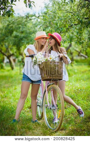 Two beautiful happy hipster girl with bikes. teenagers laughing and posing for the camera.