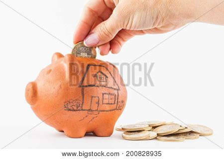 Close up of a woman saving money into a traditional clay piggy bank for a house