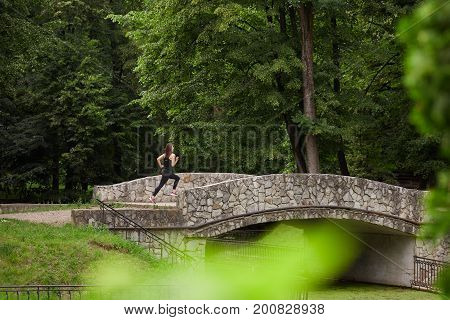 Side view of unrecognizable girl running on bridge in lush green park. Fitness woman. Fitness woman in the city park. Caucasian female fitness model working out in the morning