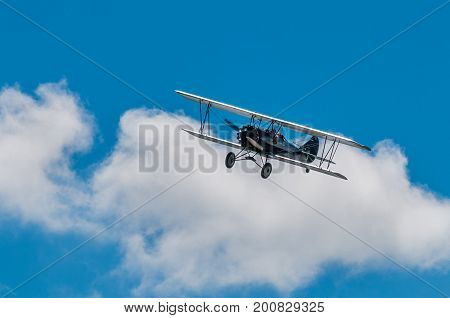 EDEN PRAIRIE MN - JULY 16 2016: 1929 Curtis-Wright Travel Air E-4000 biplane flies against one cloud at airshow. This biplane is flown by a MN based company for historic flight experiences by passengers.