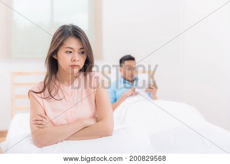 Unhappy young Asian couple having argument and quarrel while boyfriend ignored and using tablet in background. Family problem concept.