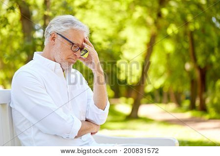 old age, retirement and people concept - thoughtful senior man in glasses sitting on bench at summer park
