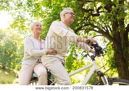 old age, people and lifestyle concept - happy senior couple riding together on bicycle at summer city park