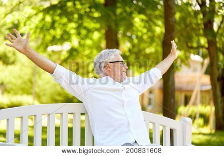 old age, retirement and people concept - happy senior man in glasses sitting on bench at summer park