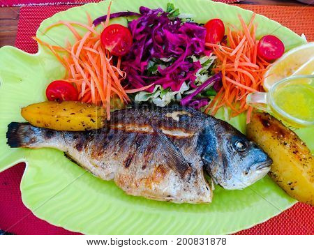Fried Dorado fish with vegetables on a plate close-up
