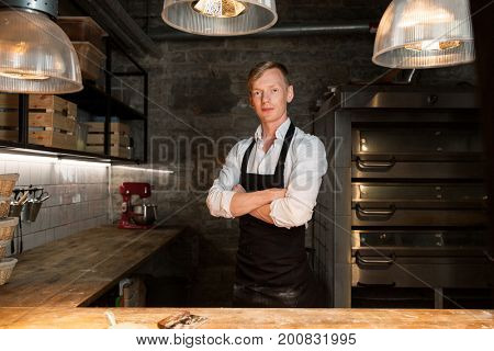 food cooking, baking and people concept - chef or baker in apron at bakery kitchen