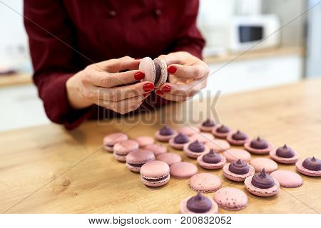 cooking, baking, confectionery and food concept - chef sandwiching baked macarons shells with cream together at pastry shop kitchen