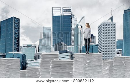 Woman in casual clothing standing on pile of documents with speaker in hand with cityscape on background. Mixed media.