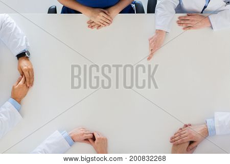 medicine, healthcare and people concept - doctor hand showing something imaginary on table