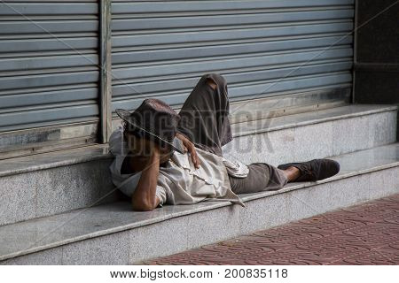 Homeless man laying on the pavement in Cambodia.