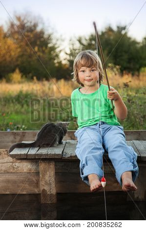 Happy boy go fishing on the river with pet, one children and kitten of the fisherman with a fishing rod on the shore of the lake