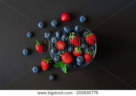Berries, summer fruit on black wooden table. Healthy lifestyle concept, blackberries in bowl, top view, close-up