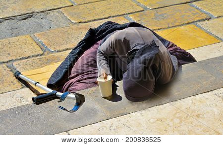 A woman in black clothes with a crutch begging for alms lying on the stairs in Europe