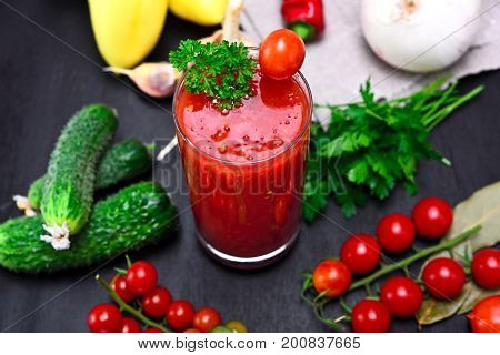 glass of freshly squeezed tomato juice on a table with vegetables top view