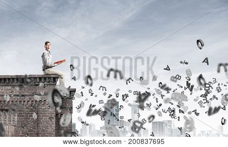 Young man in casual sitting on building top with red book in hands