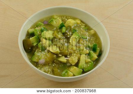 Homemade chunky avocado tomatillo salsa verde sauce or dip in white bowl
