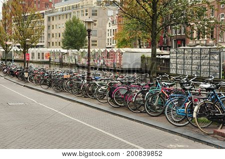 Amsterdam Netherlands,October 14th 2010.Hundreds of bicycles lined up next to one of Amsterdam's canals,with flower shops hotels and businesses.Come to Amsterdam and ride a bike along with everyone else.