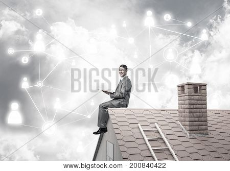 Young businessman sitting on house brick roof with red book in hands