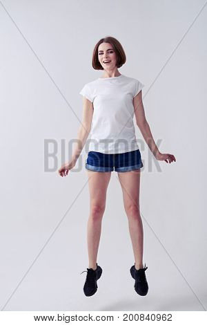 Vertical of cheerful chestnut jumping while posing in studio with copy space