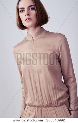 Fashion portrait of nice model posing in beige overalls in studio