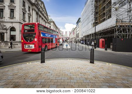 LONDON ENGLAND - JUNE 15 2016: Horizontal picture of traditional red bus and telephone cabin in London.