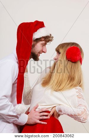 Portrait of happy smiling cute couple. Pretty woman in earmuffs and handsome man in santa claus hat on gray. Christmas xmas season.