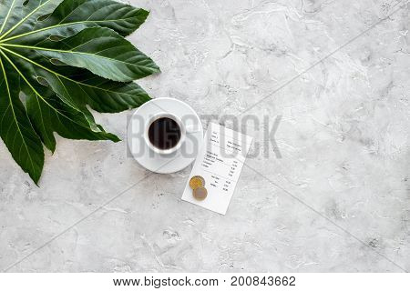 Pay restaurant bill. Bill, bank card, coins near cup of coffee on light table top view.