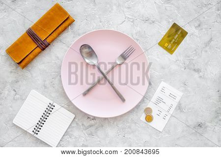 Meal is over. Bill near plate with crossed spoon and fork on grey stone table top view.