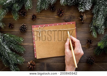 Mockup for new year 2018. Hand writes on sheet of paper near spruce branches, pine cone on wooden background top view.
