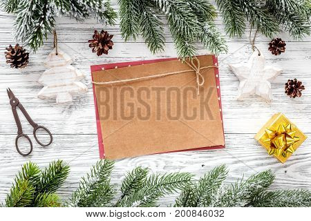 Space for new year greeting. Paper near christmas toys and spruce branches on light wooden background top view.