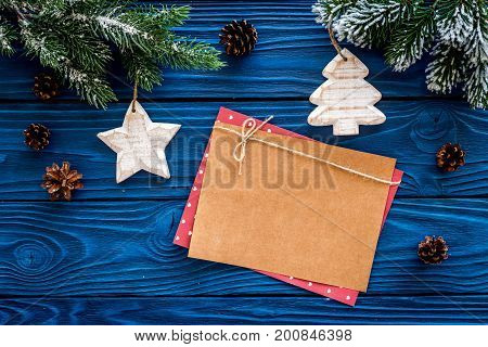 Space for new year greeting. Paper near christmas toys and spruce branches on blue wooden background top view.