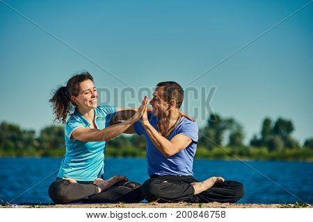 Healthy man and woman practicing padmasana pose near river