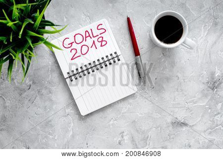 Set a goal for new year. Notebook near pen and cup of coffee on grey stone background top view.