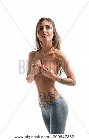 Fitness tattooed model topless wearing leggings isolated shot
