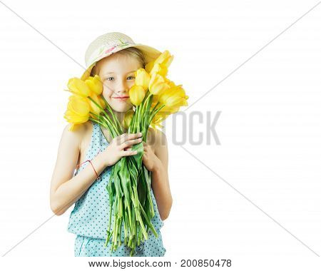 Beautiful girl in hat playing with yellow tulips isolated on a white background. The concept of a happy childhood.