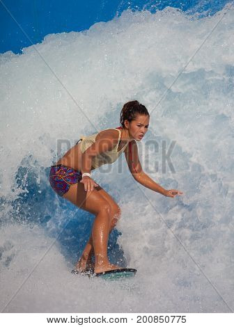 Sentosa Singapore - June 19 2010: Woman surf flowboarding at Wave House Sentosa