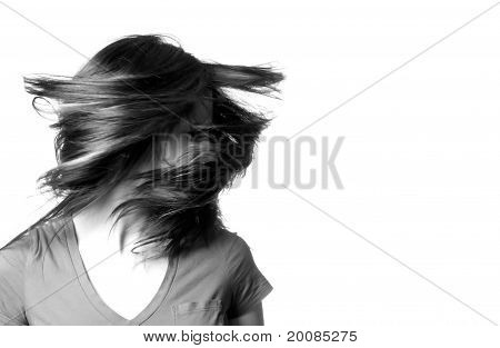 A Young Woman Shaking Her Head With Her Hair Flying Around Her.