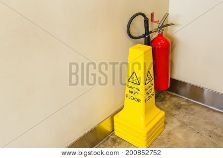 Caution wet floor yellow warning sign stands on urban ground closeup photo