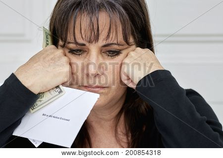 Middle Aged Woman Panicking While Holding Bills Due And Currency